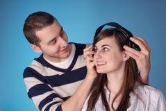 Attraktive junge Paare hören Musik stockfotos