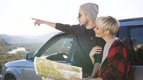 Attraktive junge Paare unter Verwendung der Karte für das Wählen der Richtung für Wanderung auf dem Gebirgshintergrund stock video footage