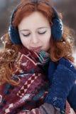 Attraktive junge rothaarige Frau mit Schnee in ihrem Haar Stockbild