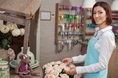 Attraktive junge Verkäuferin arbeitet in der Blume Lizenzfreie Stockbilder