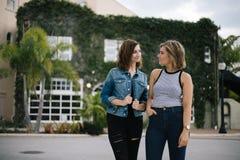 Attraktive junge weibliche beste Freunde, die Spaß vor überwuchertem städtischem Gebäude modellieren und haben lizenzfreie stockbilder