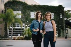 Attraktive junge weibliche beste Freunde, die Spaß vor überwuchertem städtischem Gebäude modellieren und haben stockfoto