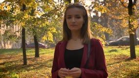 Attraktive junge weibliche Stellung im Park, gelbes Blatt halten und thoughfully schauen auf Kamera in einem schönen sonnigen stock video footage