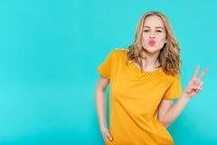 Attraktive kühle junge Frau, die einen Kuss durchbrennt und Friedenszeichenhandzeichen macht Stockfotos