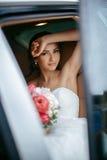 Attraktive kaukasische Braut, die im Auto und im Lächeln zur Kamera sitzt Lizenzfreie Stockbilder