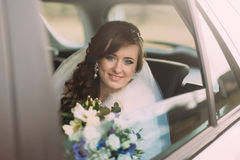 Attraktive kaukasische Braut im Hochzeitsautolächeln zur Kamera lizenzfreies stockbild