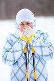 Frau, die gefrorene Hände mit Skipfosten wärmt Lizenzfreie Stockfotografie