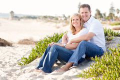 Attraktive kaukasische Paare, die am Strand sich entspannen lizenzfreie stockbilder