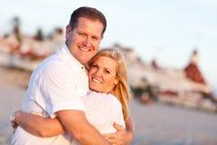Attraktive kaukasische Paare, die am Strand umarmen Lizenzfreie Stockbilder