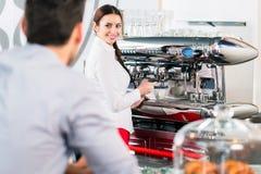 Attraktive Kellnerin, die zum männlichen Kunden beim besonders sich vorbereiten lächelt Lizenzfreies Stockbild