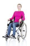 Attraktive lächelnde behinderte Frau, die in einem Rollstuhl sitzt stockfotografie