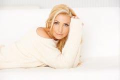 Attraktive lächelnde blonde Entspannung auf einem Sofa Stockfotografie
