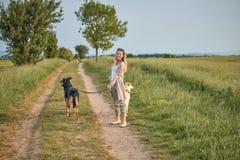 Attraktive lächelnde blonde Frau mit ihren zwei Hunden Lizenzfreie Stockbilder