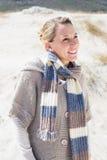 Attraktive lächelnde blonde Stellung auf dem Strand Stockfotos