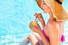 Attraktive lächelnde Brunettefrau im Sommer mit Cocktail Stockfotografie