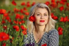 Attraktive lächelnde Frau auf dem roten Mohnblumengebiet genießend und glücklich Stockbilder