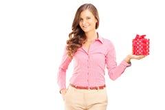 Attraktive lächelnde Frau, die eine Geschenkbox und eine Aufstellung hält Stockfoto