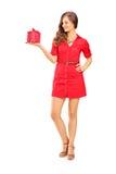 Attraktive lächelnde Frau im roten Kleid, das ein Geschenk hält Stockfotografie