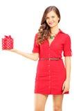 Attraktive lächelnde Frau im roten Kleid, das eine Geschenkbox hält Stockbilder