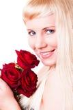Attraktive lächelnde Frau mit roten Rosen Lizenzfreies Stockfoto