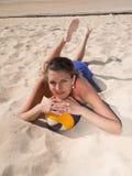 Attraktive lächelnde Frauen, die in den Sand legen Stockfoto