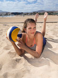 Attraktive lächelnde Frauen, die in den Sand legen Lizenzfreie Stockbilder