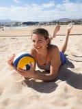 Attraktive lächelnde Frauen, die in den Sand legen Stockbild