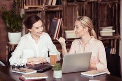Attraktive lächelnde Geschäftsfrauen, die am Schreibtisch sprechen stockfotografie