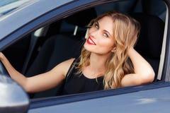 Attraktive lächelnde junge blonde Frau hinter dem Rad Stockfoto