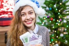 Attraktive lächelnde junge kaukasische Frau mit Euro lösen Hände als Geschenk am Weihnachtsabend ein Stockfoto