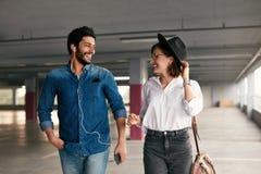 Attraktive lächelnde Paare in der bequemen Kleidung am Parken lizenzfreie stockbilder