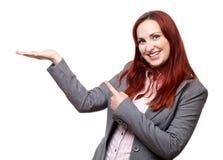 Attraktive lächelnde und zeigende Frau stockfotos
