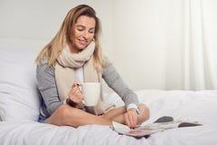 Attraktive lächelnde zufrieden gestellte junge Frau, die eine Zeitschrift liest Stockbilder