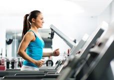 Attraktive Lack-Läufer der jungen Frau auf einer Tretmühle Stockbilder