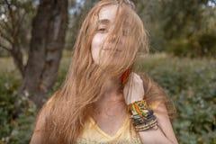 Attraktive langhaarige blonde Mädchen boho Artarmbänder verstecken Hälfte ihres Gesichtes durch Haar Lizenzfreie Stockbilder