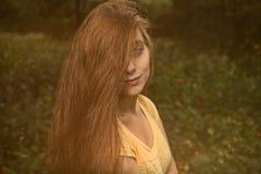 Attraktive langhaarige blonde Mädchenfellhälfte ihres Gesichtes durch Haar Stockfotos