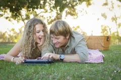 Attraktive liebevolle Paare unter Verwendung einer Noten-Auflage draußen Stockfotos