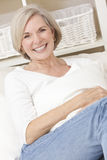 Attraktive ältere Frau, die sich zu Hause entspannt Stockbilder