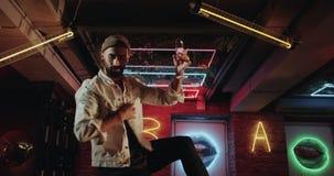 Attraktive Männer mit einem Barttanzen und mit einem Glas Champagner auf dem Bartisch im dunklen Café mit Discolichtern stock footage