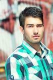 Attraktive Mannaufstellung im Freien über Graffitiwand lizenzfreie stockfotos