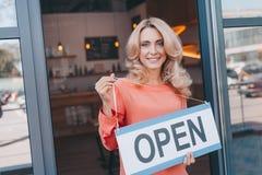 attraktive Mitte gealterter Kleinunternehmer, der Zeichen offen und das Lächeln hält lizenzfreies stockfoto