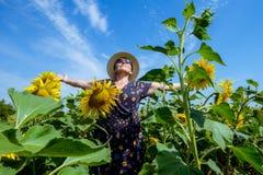 Attraktive Mittelalterfrau im Strohhut mit den Armen streckte im Sonnenblumenfeld aus und feierte Freiheit Positives Gefühlglaube Lizenzfreies Stockbild