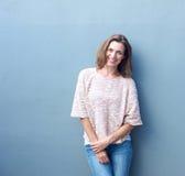 Attraktive mittlere erwachsene Frau, die auf grauem Hintergrund lächelt Lizenzfreie Stockfotos