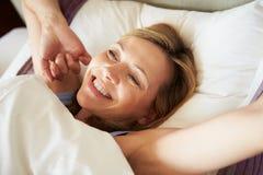 Attraktive mittlere Greisin, die im Bett aufwacht Stockbilder