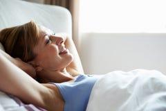 Attraktive mittlere Greisin, die im Bett aufwacht Lizenzfreie Stockfotografie