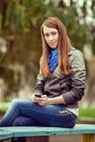 Attraktive modische junge Frau, die auf einer Bank sitzt Stockbilder