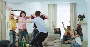 Attraktive multi ethnische Freundkerle und -damen, die im dem Fernsehen ein Fußballspiel sie den Sieg von feiernd aufpassen stock video footage