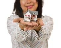 Attraktive multiethnische Frau, die kleines Haus anhält Lizenzfreie Stockbilder