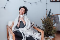 Attraktive nette Frau, die nahe Weihnachtsbaum in der Decke mit Tasse Tee oder Kaffee und Träumen sitzt Neues Jahr ` s Eve stockfoto