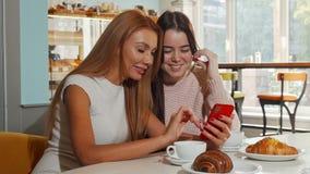 Attraktive nette Frauen, die zusammen zur Kamera, unter Verwendung des intelligenten Telefons lachen stock footage